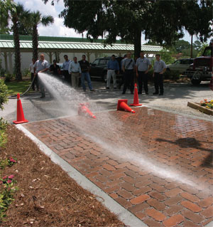 Pavers create a pervious surface that, unlike asphalt or concrete, allows water to seep into the ground at the site. This eliminates runoff and keeps pollutants out of area waterways. As part of a demonstration of the Lowcountry Paver Permeable Pavement test pad, The Bluffton Township Fire Department sprayed 2,000 gallons of water onto a 12' x 18' section of pavers. An entire truckload of water was filtered through the ground in 18 minutes. More than 40 local architects, engineers, Township managers and developers attended the demonstration. (Photo courtesy Lowcountry Paver).